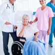 Serious medical team taking care of a senior woman — Stockfoto