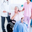 Smiling medical team taking care of a senior woman - Stock Photo