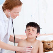 Pretty doctor examining a little boy — Stock Photo