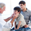 Senior doctor examing little boy throat with his father — Stock Photo