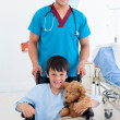 Portrait of a cute little boy sitting on wheelchair and a doctor - Stock Photo