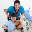 Portrait of a little boy sitting on wheelchair and a doctor — Stock Photo #10296122