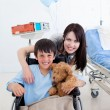Stock Photo: Smiling little boy sitting on wheelchair and his mother
