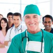 Assertive senior surgeon standing with his colleagues — Stock Photo #10296128