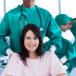 Ethnic surgeon carrying a female patient on a wheelchair - Stock Photo