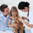 Smiling patient examining a teddy bear with a doctor — Stock Photo #10296219