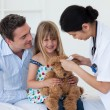 Smiling patient examining a teddy bear with a doctor — Stock Photo