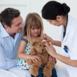 Portrait of a doctor and little girl examing a teddy bear — Stock Photo