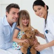 Portrait of a doctor and happy little girl examing a teddy bear — Stock Photo