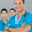Stock Photo: Portrait of an attractive doctor with his colleagues in the back