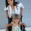 Royalty-Free Stock Photo: Portrait of a little girl on a wheelchair and a young doctor