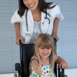 Young female doctor and Smiling girl on a wheelchair with thumb — Stok fotoğraf