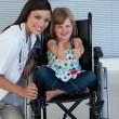 Portrait of a little girl on a wheelchair with her doctor — Stock Photo