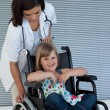 Female doctor pushing wheelchair — Stock Photo #10296339