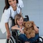 Little girl on a wheelchair holding her teddy bear — Stock Photo