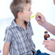 Child taking cough medicine - Foto Stock