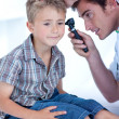 Doctor examining a patient' s ears with a otoscope — Stock Photo #10296365