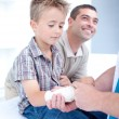 Stock Photo: Bandaging an arm injury on a child