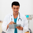 Young male Doctor holding a clip board - Stock fotografie