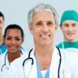 Stock Photo: Senior doctor standing in front of his team