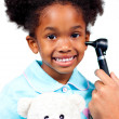 Smiling little girl attending medical check-up holding a teddy b - Stock Photo