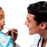 Male doctor checking little girl's throat — Stock Photo