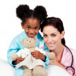 Cute little girl with her doctor smiling at the camera — Stockfoto