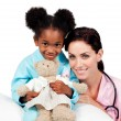Cute little girl with her doctor smiling at the camera - Stock Photo
