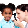 Stock Photo: Smiling doctor checking her patient's ears