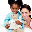 Smiling little girl with her nurse looking at the camera — Stock Photo