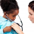 Cute little girl and her doctor playing with a stethoscope — Stock Photo