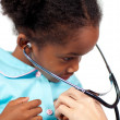 Little girl playing with a stethoscope at a medical check-up — Stock Photo