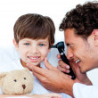 Smiling doctor examining patient's ears - Stock Photo