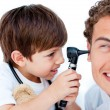 Cute little boy playing with his doctor - Stock Photo