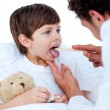 Male doctor checking little boy's throat — Stock Photo