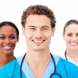 Smiling young doctors standing in a row — Stock Photo