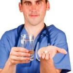 lekarz trzymając tabletkę i szklankę wody — Zdjęcie stockowe