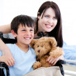 Smiling little boy in a wheelchair with his mother — Stock Photo #10296834