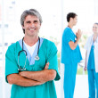 MAture male doctor standing with his team — Stock Photo