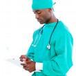 Charismatic male surgeon making notes in a patient's folder — Stock Photo #10296882