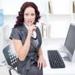Young businesswoman shushing with her finger in office - Stock Photo