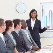 Businesswoman giving a presentation to her colleagues - Stock Photo