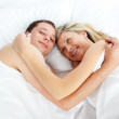 Couple lying in bed and smiling at the camera — Stock Photo