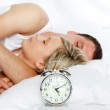 Couple in bed with focus in alarm clock — Stock Photo