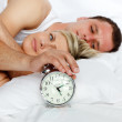 Couple in bed with alarm clock going off — Stock Photo