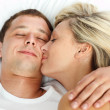 Girlfriend kissing her boyfriend in bed — Stockfoto
