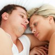 Intimate couple relaxing in bed — Stock Photo