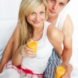 Couple drinking orange juice in bed - Foto Stock