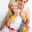Couple holding orange juice glasses in bed - Foto Stock