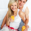 Couple holding orange juice glasses in bed — Stock Photo